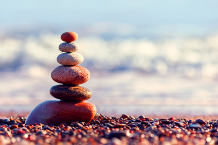 Pyramid of colorful, balanced stones on the sea background. Concept of harmony and balance. Soft focus, selective focus